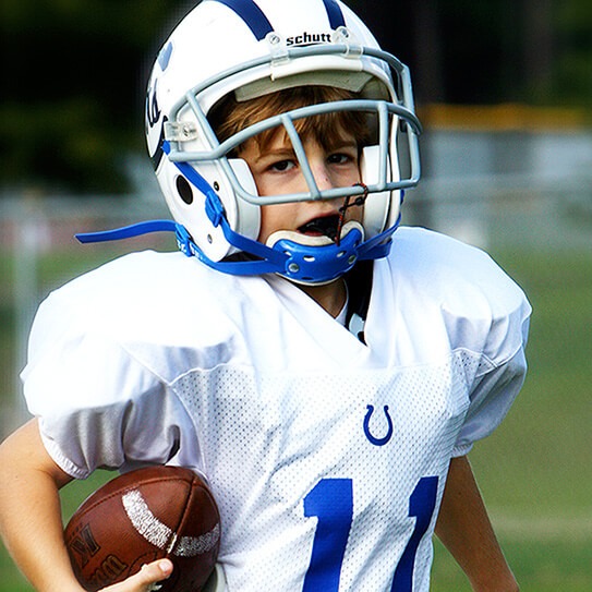 kid playing football with mouthguard